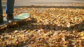 Teen rides a skateboard through fallen autumn leaves in the park. Teen rides a skateboard through fallen autumn leaves stock video footage