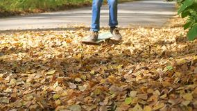 Teen rides a skateboard through fallen autumn leaves in the park stock video footage