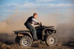 Teen riding ATV quad. Teenager riding ATV quad - four wheeler in the hills kicking up dirt Royalty Free Stock Photos