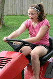 Teen Riding Mower. Youth Teen Riding Lawn Tractor Mower in back yard with music head phones on Royalty Free Stock Images