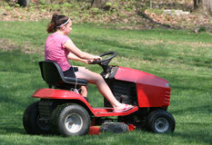 Teen Riding Mower. Youth Teen Riding Lawn Tractor Mower in back yard Stock Image