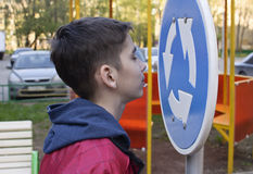 Teen and the road. Teen looks at the road sign Stock Image