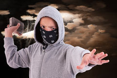 A teen with a rock, in a act of juvenile delinquen. Cy, with clouds of smoke background royalty free stock image