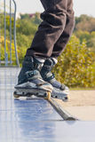 Teen with roller skates performing a stunt on a half pipe ramp. Stock Photos