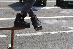 Teen with roller skates performing a stunt on a half pipe ramp Stock Photography