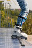 Teen with roller skates starting a stunt on a half pipe ramp. Stock Photos