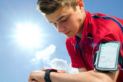 Teen runner checking settings on smart watch. Royalty Free Stock Photos