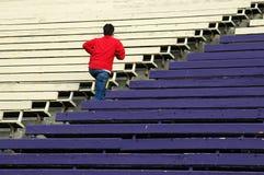 Teen Running. Up some bleachers in a stadium Stock Photo
