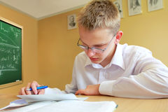 Male Pupil Studying. At Desk In Classroom Writing and Reading Royalty Free Stock Photo