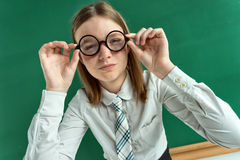 Teen school girl in uniform near blackboard. Wearing glasses, creative concept with Back to school theme Royalty Free Stock Photos