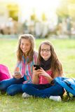 Teen schoolgirls having fun with mobile phone Royalty Free Stock Images
