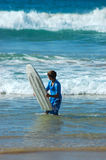 Teen in sea with surfboard. Male teenager surfer in sea with surfboard, waves in background Royalty Free Stock Photos