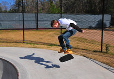 Teen Shadow Skater. A teen skater flys high on his skateboard at a skatepark stock photo