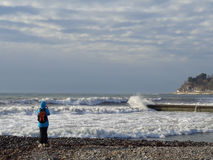Teen shooting the storm. Teen with backpack watching  great sea waves from the beach Stock Image