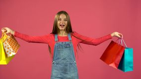 Teen with bags in their hands and rejoices at their purchases. Pink background. Teen after shopping comes with bags in their hands and rejoices at their stock video footage