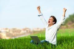 Teen shouting of joy outdoors. Happy teen with laptop in green field shouting of joy Stock Photo