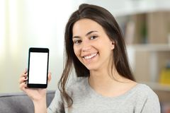 Teen showing a mockup phone screen to camera. Sitting on a couch in the living room at home Royalty Free Stock Images