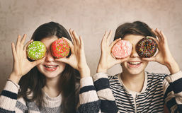 Teen siblings boy and girl with dough nut eyes. Teen siblings boy and girl with doughnuts eyes smiling close up portrait Stock Photos