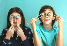 Teen siblings boy and girl kids with sushi rolls Royalty Free Stock Photos