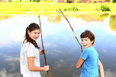 Teen siblings kids boy and girl fishing. On the lake close up photo Royalty Free Stock Photography