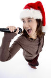 Teen singer with mic and christmas hat Royalty Free Stock Photo