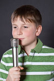 Teen singing into a microphone Royalty Free Stock Photos