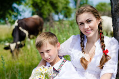 Teen sister and little brother sitting by cow herd Royalty Free Stock Image