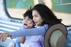 Teen sister taking care of disabled little brother, pointing off Royalty Free Stock Photography