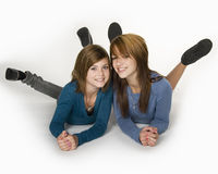 Teen sisters. Two teenage girls lying on floor with feet in air Stock Photography