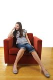 Teen sit in a sofa. Teen with long legs sit in a orange sofa Stock Photos