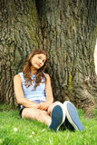 Teen sit on a tree Royalty Free Stock Image