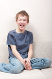 Teen sits on  couch and laughs Royalty Free Stock Photography