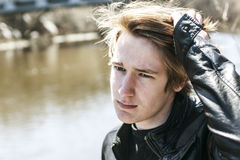 Teen sits outside close to a bridge Leather jacket. Royalty Free Stock Images