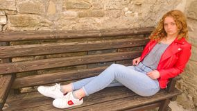 Teen sitting on bench stock image