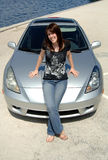 Teen sitting on car hood. A happy young woman in jeans and t-shirt sitting on the hood of her car stock photos