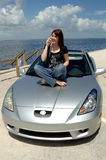 Teen sitting on car hood on cell phone. A happy young woman in jeans and t-shirt sitting on the hood of her car talking on her cell phone at the beach stock images