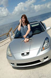 Teen sitting on car hood on cell phone. A happy young woman in jeans and t-shirt sitting on the hood of her car talking on her cell phone at the beach royalty free stock photography
