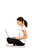 Teen sitting cross legged with laptop. Royalty Free Stock Photography