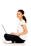 Teen sitting cross legged with laptop. Stock Image