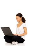 Teen sitting cross legged with laptop. Royalty Free Stock Image