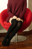 Teen sitting on red armchair. A teenager is sitting on a round armchair wearing over the knee black socks and a bordeaux dress Stock Photo