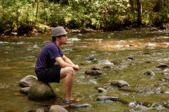 Teen sitting on river rocks, side view Stock Photography