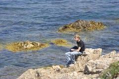 Teen sitting on rocks Stock Photography