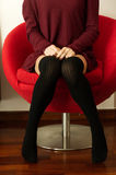Teen sitting. A teenager is sitting on a red armchair wearing over the knee black socks Royalty Free Stock Photos