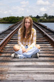 Teen sitting on train tracks Royalty Free Stock Image