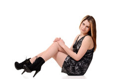 Teen sitting and wearing high heel boots Royalty Free Stock Images