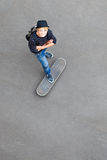 Teen skateboarder. Happy teen skateboarder standing on skateboard and looking up Royalty Free Stock Photo