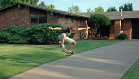 Teen Skater Airborne. A teenage boy soars through the air on his skateboard on the driveway of a suburban home Stock Images