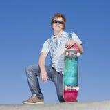 Teen skater atop ramp. Teen skater kneels atop ramp with skateboard and smiles Royalty Free Stock Photos
