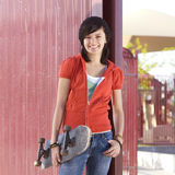 Teen skater girl. Teen girl with skateboard hangs out at the park Stock Image